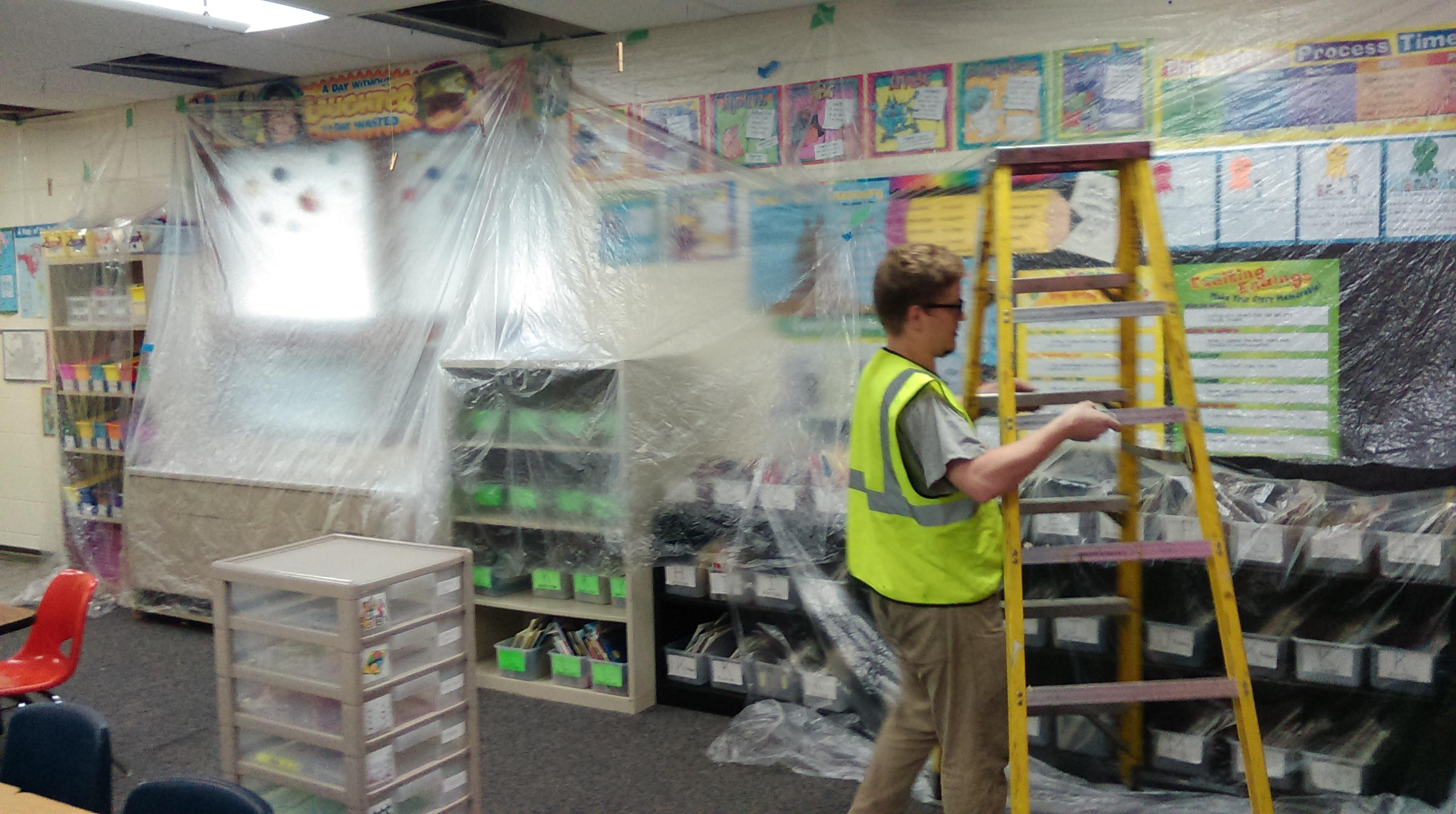 Accurate-Airtight Exteriors worker putting plastic up in a classroom to keep everything clean