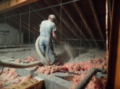 A technician applying blown insulation