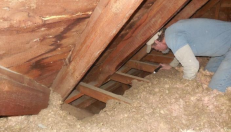 Worker in attic inspecting insulation