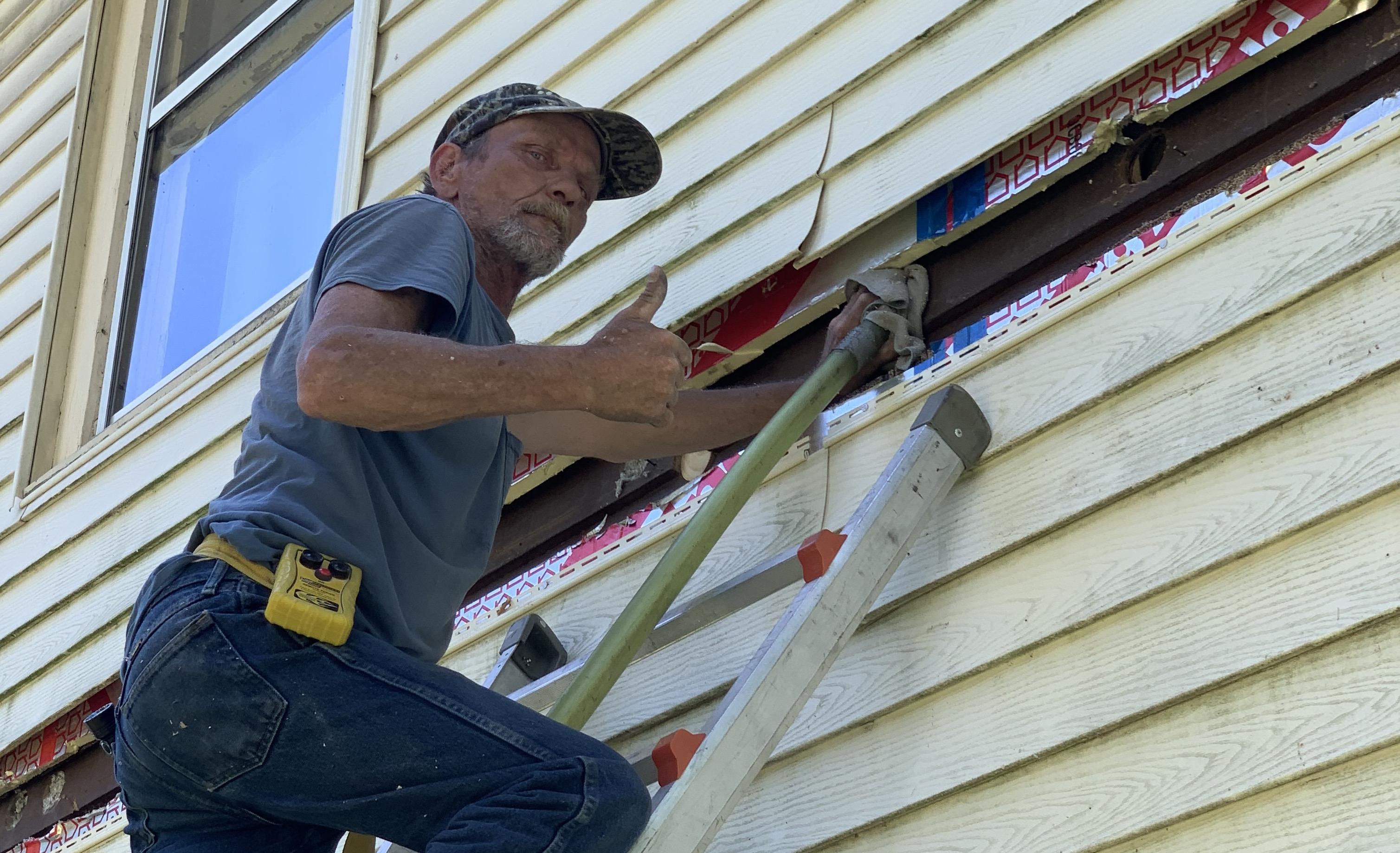 Accurate-Airtight Exteriors Crew Member Giving A Thumbs-Up While Applying Blown-In Cellulose Insulation