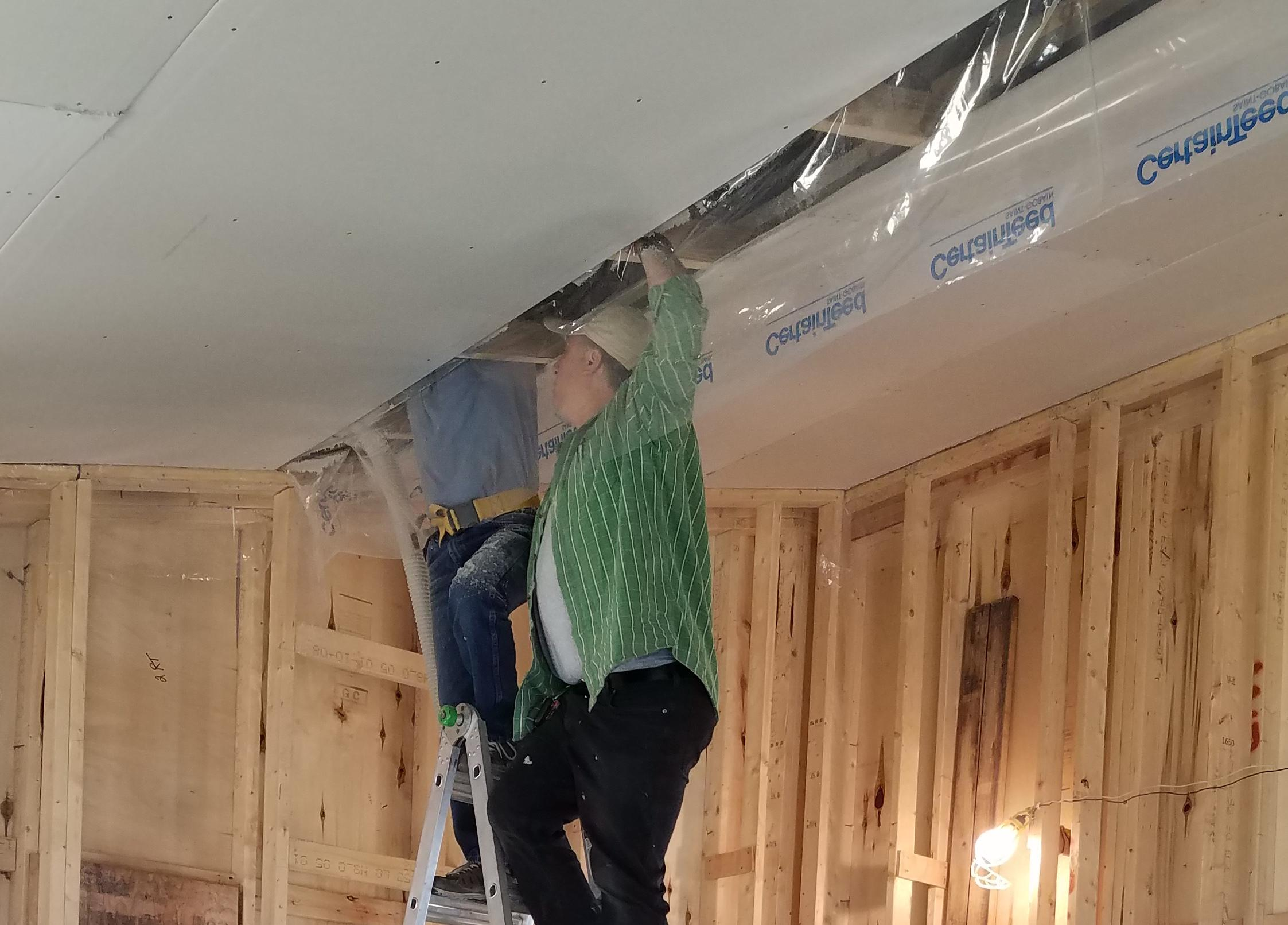 Accurate-Airtight Exteriors' President, Torrance Kramer, working from a ladder to install cellulose insulation
