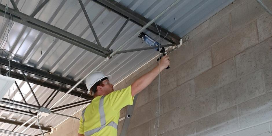Worker applying caulk to commercial ceiling